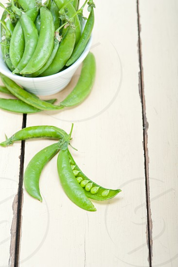hearthy fresh green peas  over a rustic wood table photo