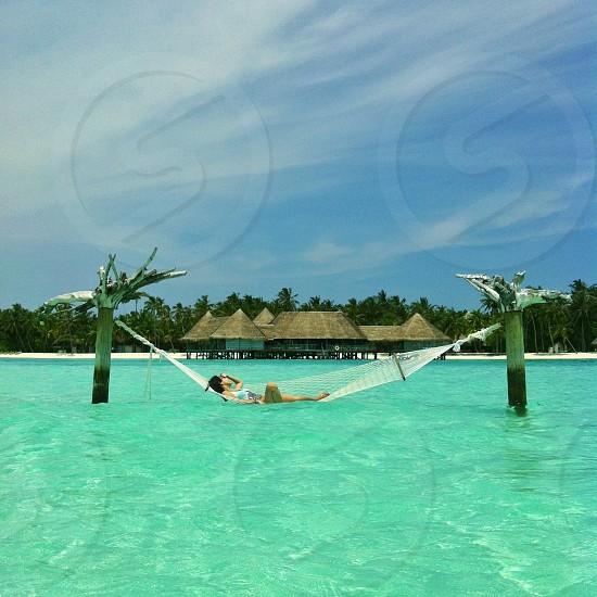 woman in white net hammock on top of water photo