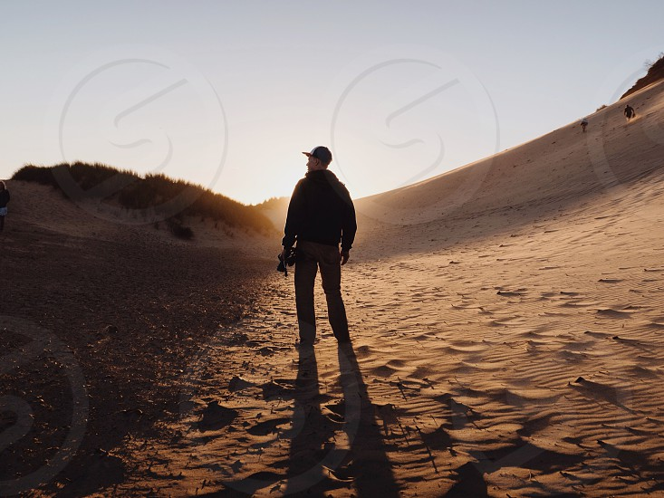 man standing in a sand dune photo