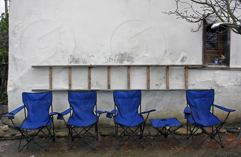 Blue folding camping chairs and table lined up in front of a rustic white wall in the country with a ladder on the wall and an old window. The concept of waiting. photo