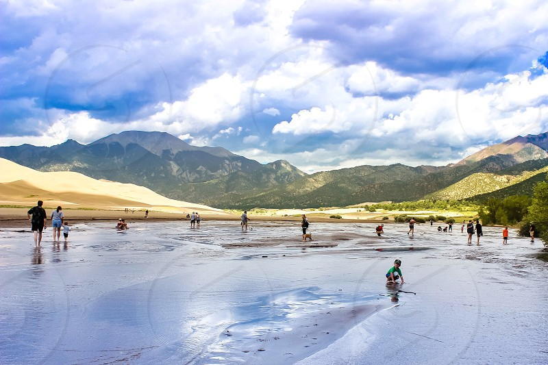 Bottom of the Great Sand Dunes where people enjoy playing and wading in the shallow stream photo