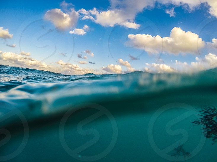 beach wave above water under water sky clouds photo