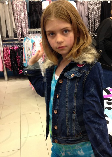 girl tries on jackets at store photo