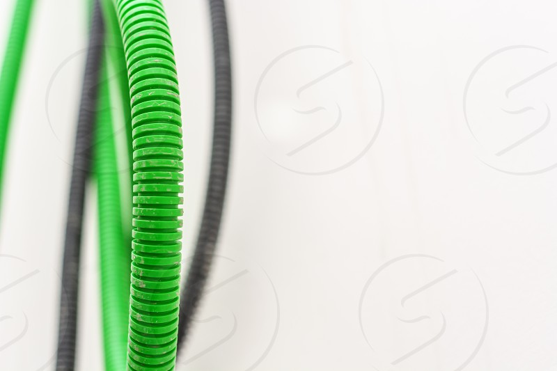 Black and green corrugated bellow conduit tube for electrical wiring photo