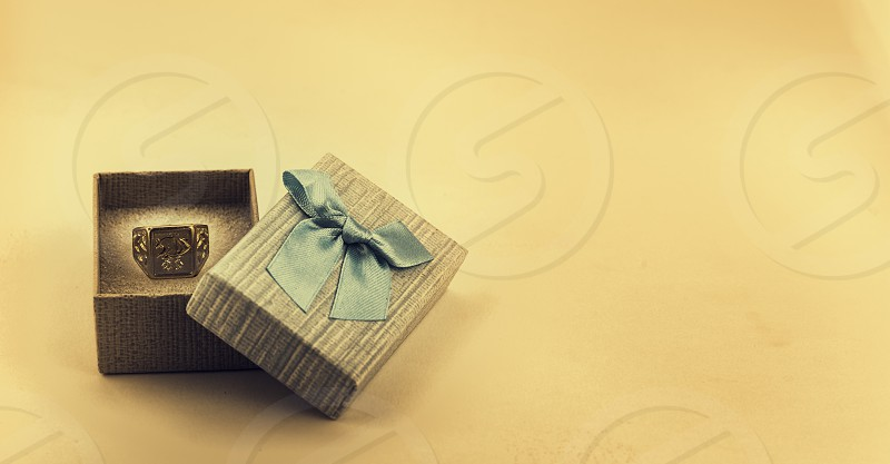Beautiful gift box and gold ring. Concept of wedding marriage wealth and luxurious lifestyle. selective focus photo