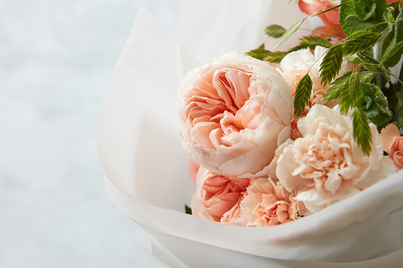 Wonderful bouquet of bush flowers wrapped in white paper. Selective focus over white background photo