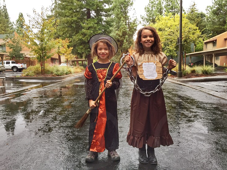 girls in costume with broom and chain photo