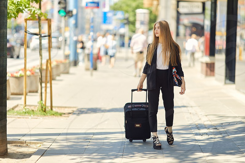 Blonde girl walking on the street with suitcase  photo