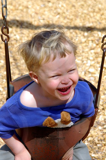 Child on a swing.  JOY.  Hilarity.  Fun.  Funny.  Laughing. photo