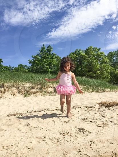 girl wearing pink halter strap top and ruffled skirt walking on white sand during daytime photo