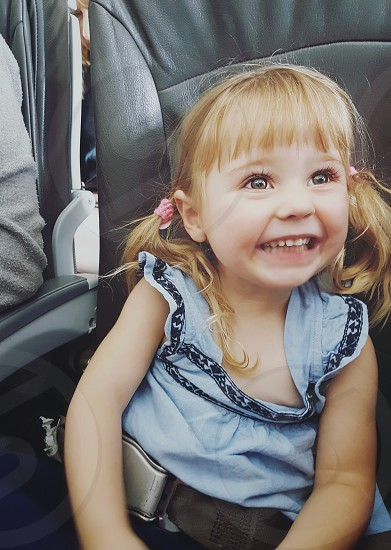 Little girl smiles happily as she ride an airplane photo