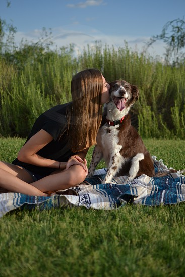 Dog and female owner outdoors in the grass being playful photo