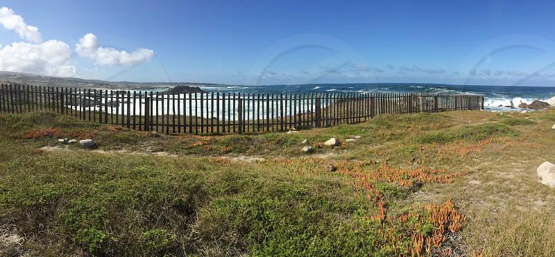 Ocean fence waves sky clouds photo