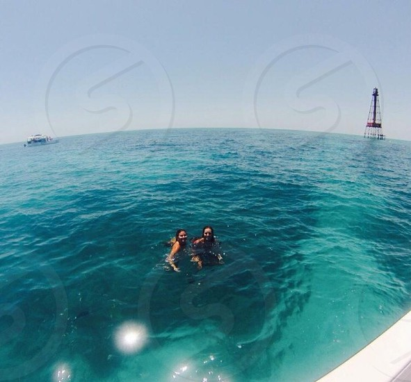 two women swimming near boat with buoy ahead photo