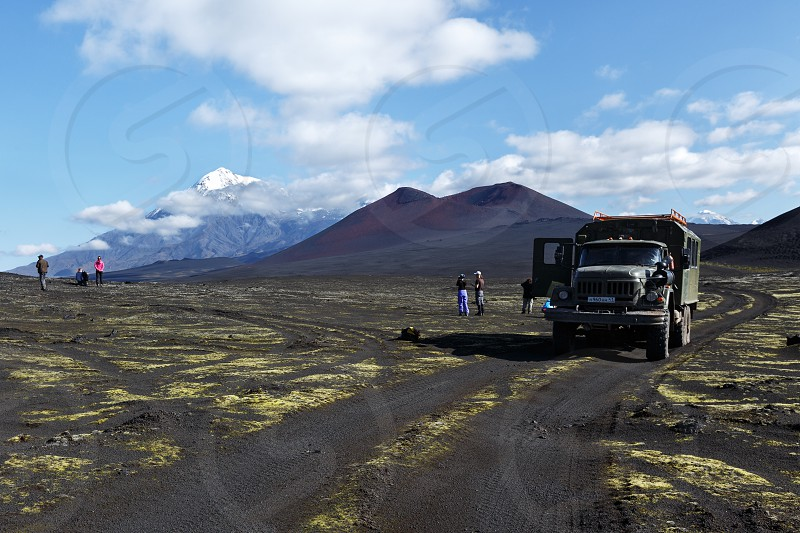TOLBACHIK VOLCANO KAMCHATKA PENINSULA RUSSIA - AUG 27 2014: Russian extreme off-road expedition truck ZIL-131 (6-wheel drive) on mountain road on background of volcanic cinder cone and beautiful volcano. Kamchatka Klyuchevskaya Group of Volcanoes photo