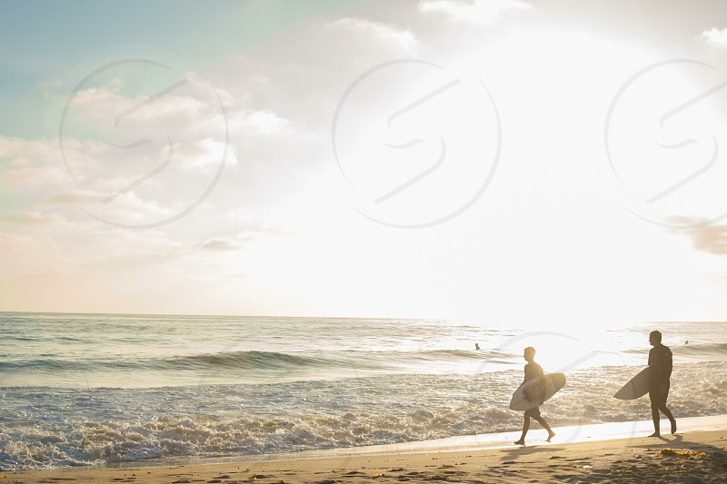 2 man carrying surfboard walking across the sea shore photo