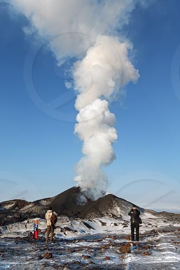 TOLBACHIK VOLCANO KAMCHATKA PENINSULA RUSSIAN FAR EAST - FEBRUARY 2 2013: Tourists watching the eruption of active Tolbachik Volcano erupting from crater lava steam gas and ash. Klyuchevskaya Group of Volcanoes Kamchatka Region. photo