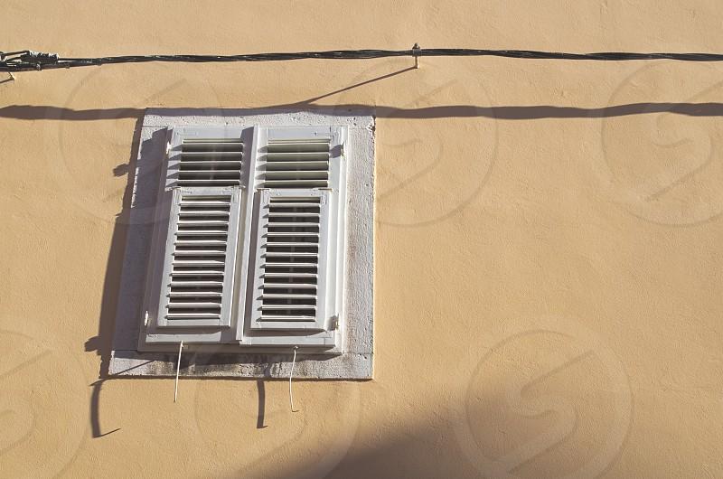 Mediterranean Style Window on a Yellow Wall photo