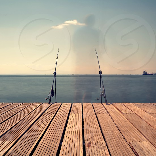 fishing rod on brown wooden dock photo