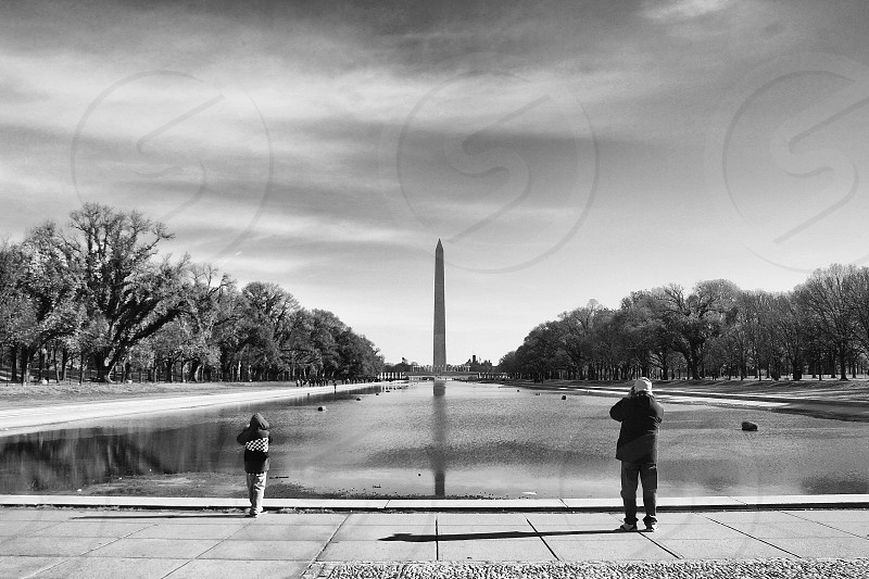 A father and small son stand at the end of the reflecting pool in DC and photograph the Washington monument. photo