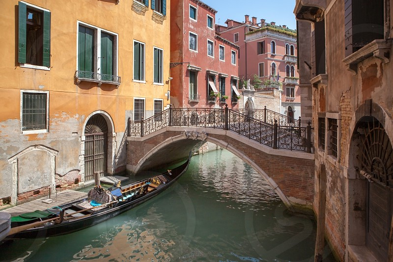 Narrow canal among old colorful brick houses in Venice Italy. Beautiful bridge in antique Venice city Italy. photo