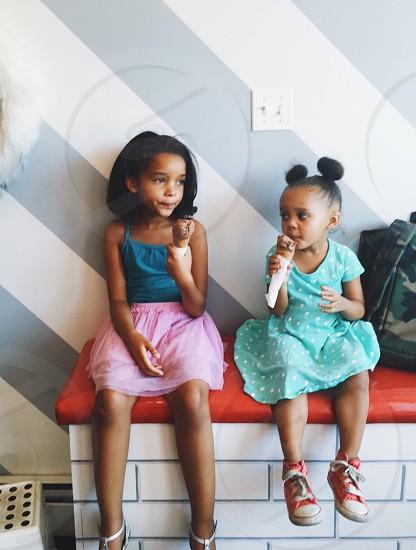 2 children sitting on a hallway desk eating ice cream photo