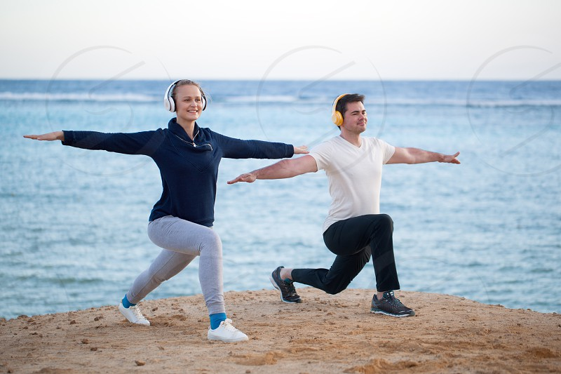 Young people having physical training at the seaside. They doing exercises while enjoying favourite music in wireless headphones photo