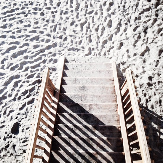 brown wooden stair on the sand photo