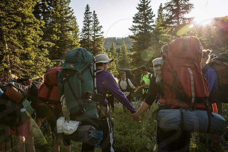 backpackers hiking in mountains in full gear photo