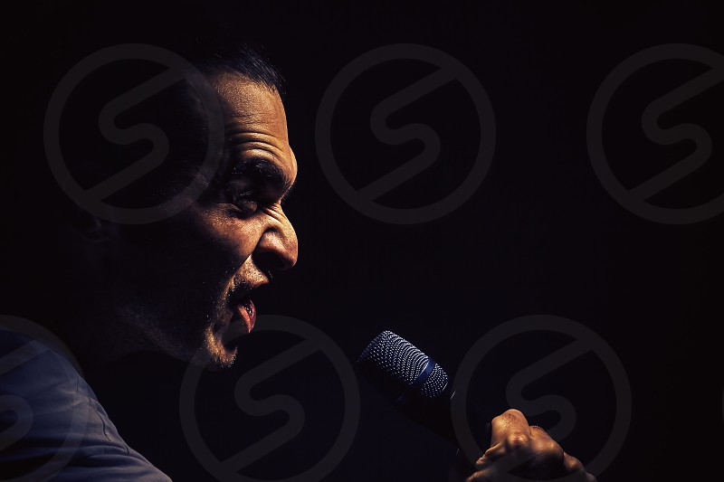 Act of a man with microphone angry facial expression.  photo