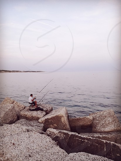 A man fishing in the beautiful Ionian Sea in Campomarino in the South of Italy photo