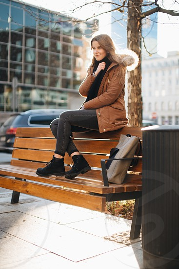 Young pretty girl sit on the bench. Hang her scarf in one hand and look around. Winter clothing with warm weather sunset scene photo