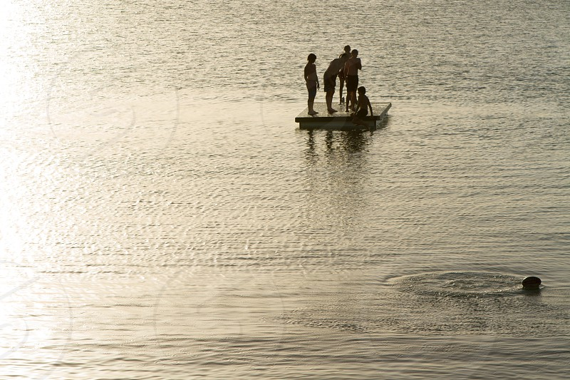 Boys playing in the lake at sunset photo