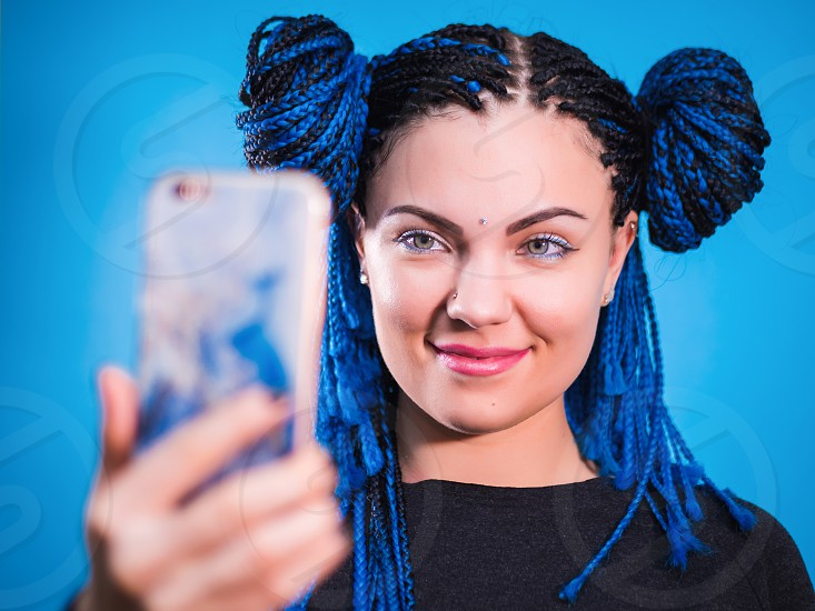 Adorable hipster caucasian female with african colorful braids hairstyle checking news feed or messaging via social networks using free wi-fi on mobile phone smiling posing on violet wall photo