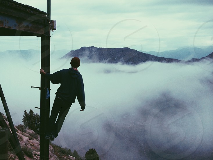 man wearing a beanie leaning off a ladder looking at fog photo