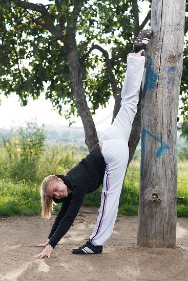 Young girl performs gym split in a city park on the summer morning photo