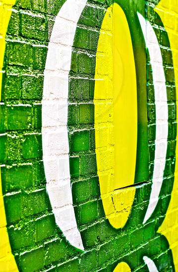 Green yellow and white painted on a brick wall. photo