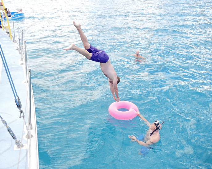 Diving from a yacht into a pink floaty in the blue ocean fun photo