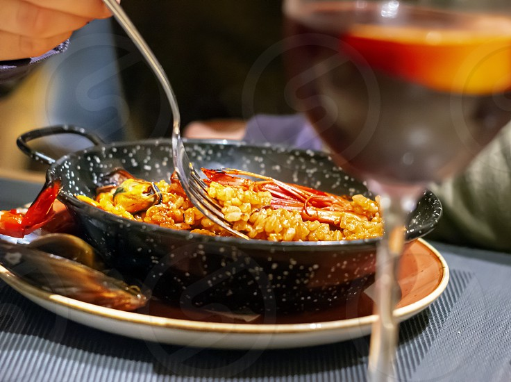 eating Valencian paella in a black pan using a fork. Typical Spanish cuisine. Seafood and tourism photo
