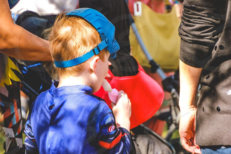 little boy wearing a superhero costume enjoying a popsicle at a festival on a sunny day  photo
