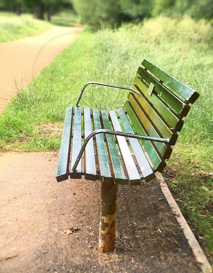 A solitary green bench in a London park photo