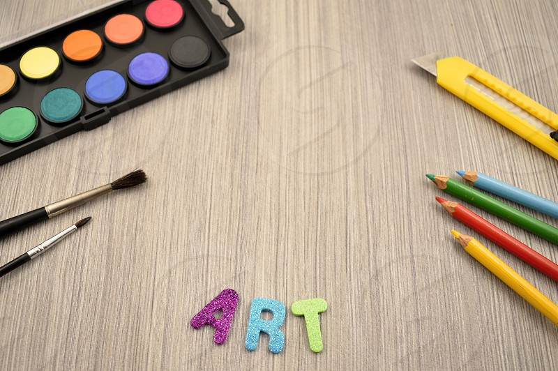 Back to school border. Art supplies on a wooden background. School supplies for painting photo