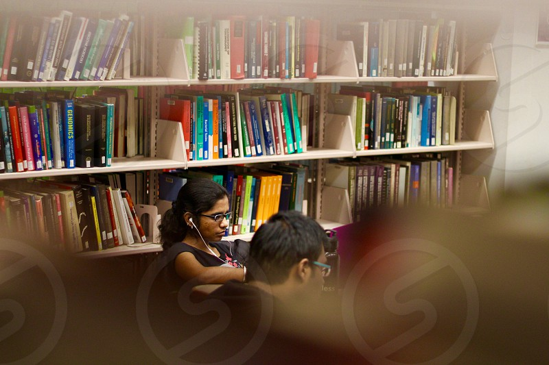 man and woman sitting beside book shelves photo