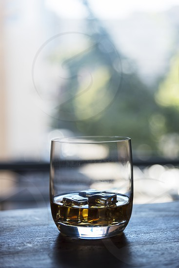 Portrait of single whiskey hero on ice drink on outside patio table with dark tones copy space above. photo