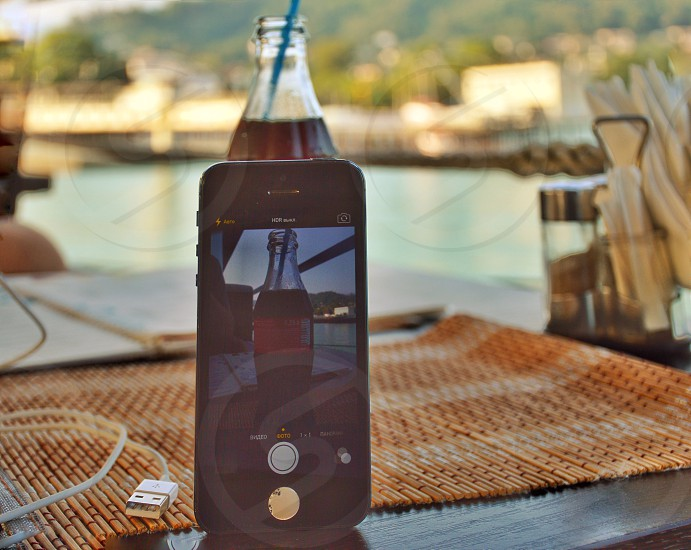 silver iphone 6 capturing shot of coca-cola glass bottle over brown wooden table during daytime photo