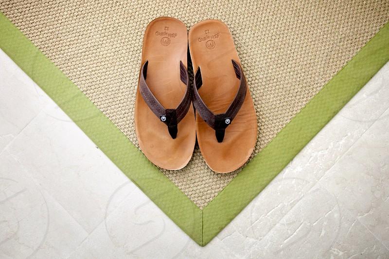 Flip flips shoes mat stone tile floor green beige brown symmetry triangle. photo