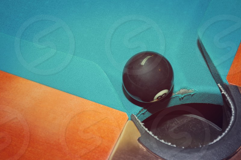 Eight Ball at the Hole on Pool Table photo