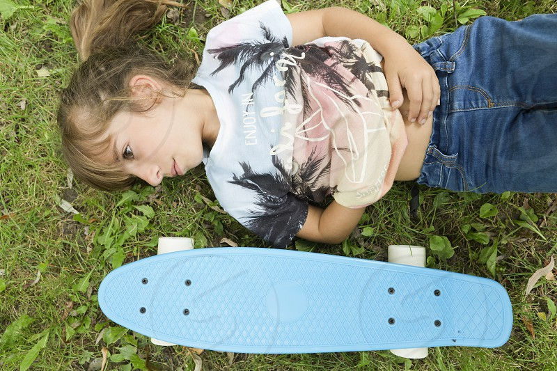 Girl lying on the grass with her skateboard in a park of Pamplona in Spain. photo