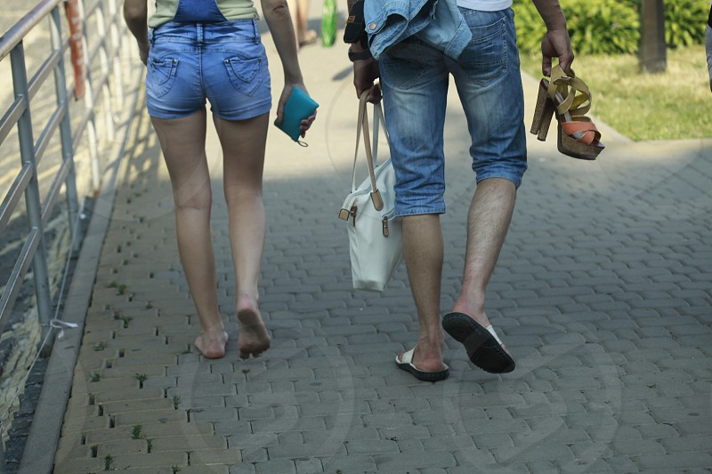 man walking while  holding women's white leather tote bag on left hand and clog sandals on right hand beside woman photo