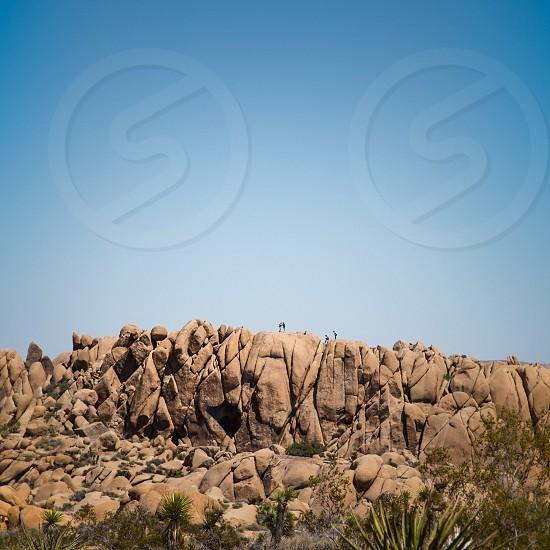 people on top of huge rock photo